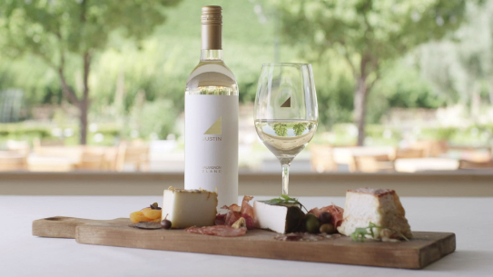 JUSTIN Wine – Lesson 5 – Crush It with JUSTIN – Pairing Wine and Food; Cheese and charcuterie board with a bottle of JUSTIN's Sauvignon Blanc and a glass of white wine